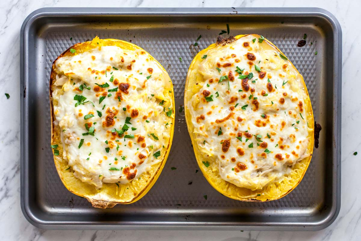 Two spaghetti squash boats on a silver sheet pan