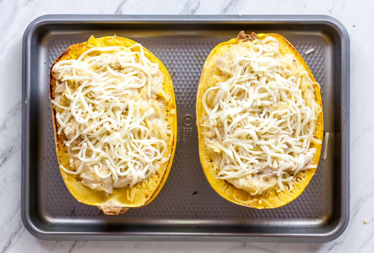 Two spaghetti squash boats on a baking sheet with shredded mozzarella cheese overtop