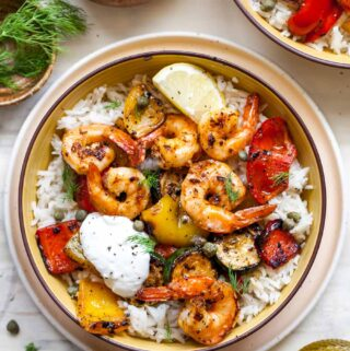 Zucchini and grilled shrimp in a bowl topped with yogurt