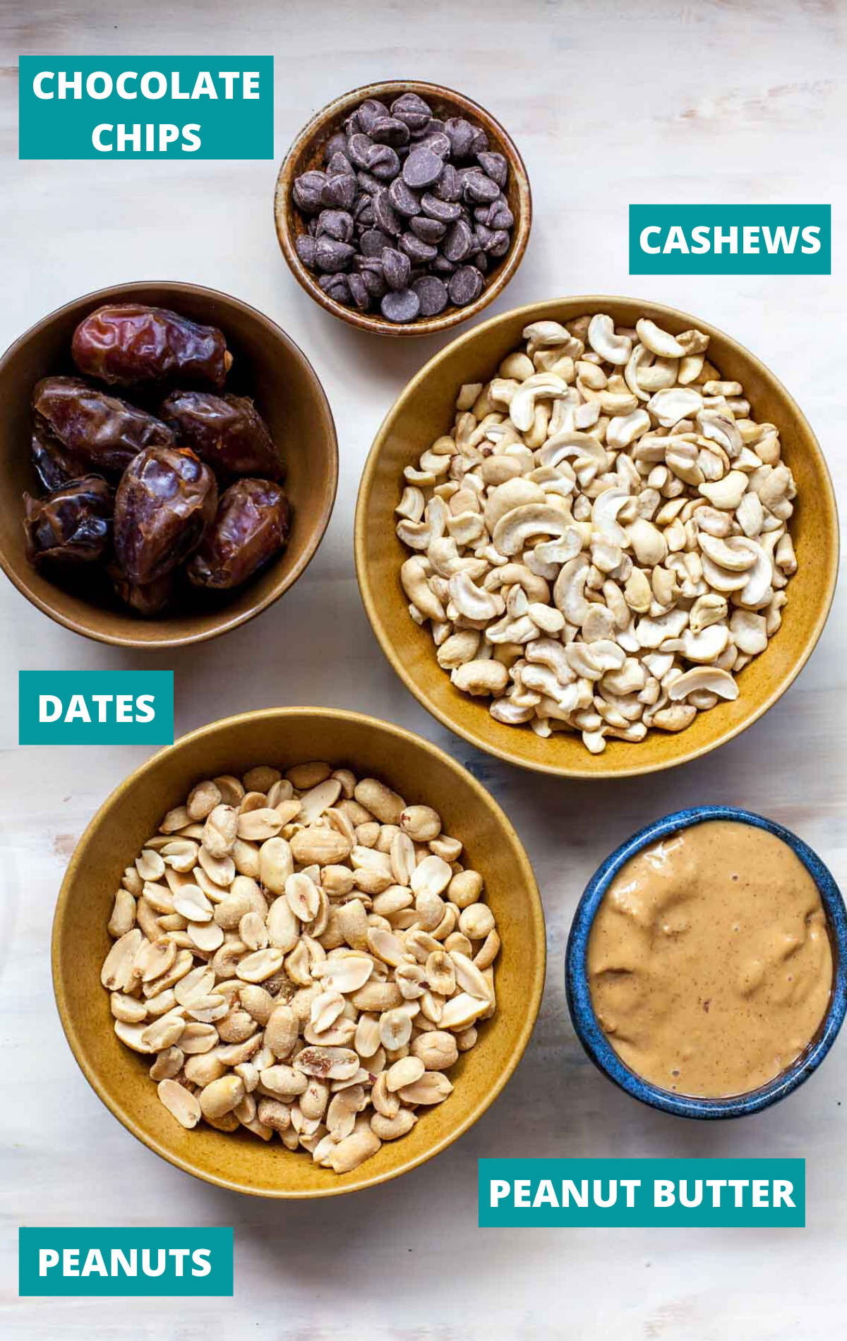 Nuts, dates, chocolate chips, and peanut butter in separate bowls on a white board