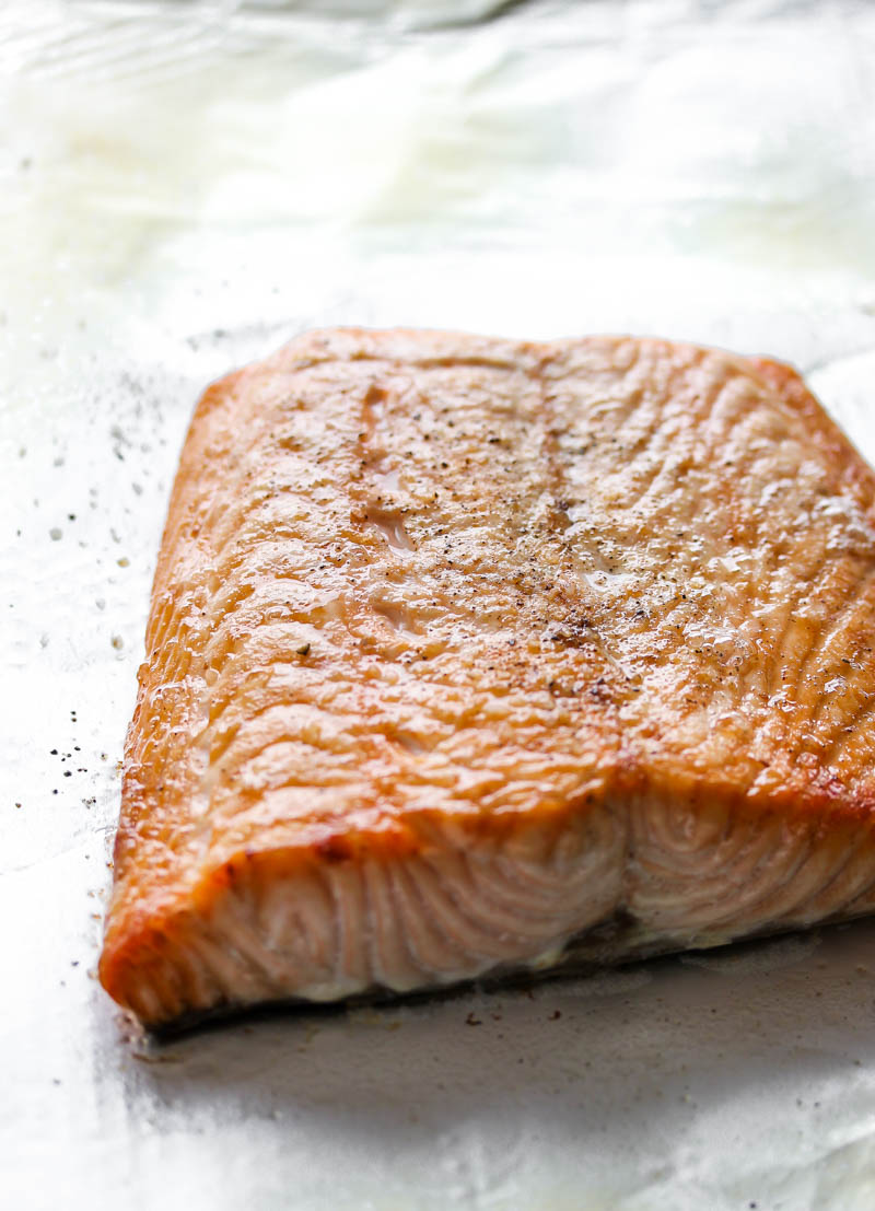 One fillet of broiled salmon in a foil-lined baking sheet