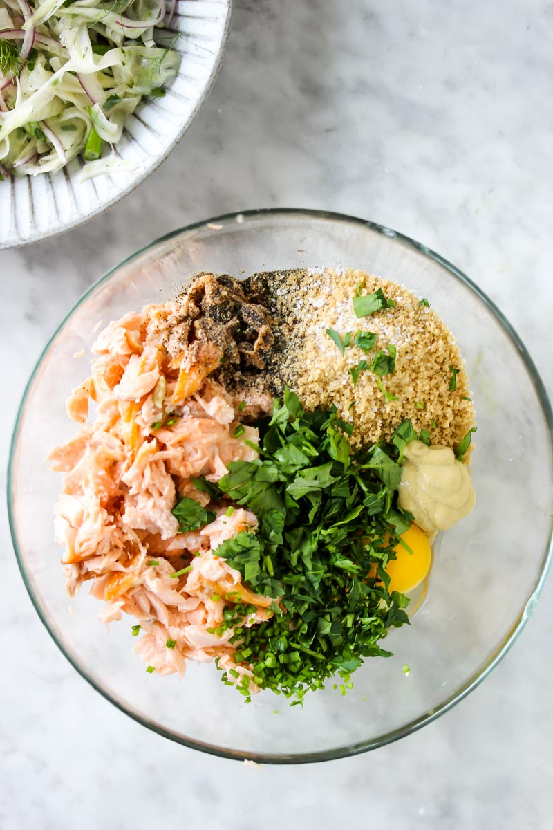 Flaked salmon, egg, breadcrumbs, and eggs being mixed in a large clear bowl
