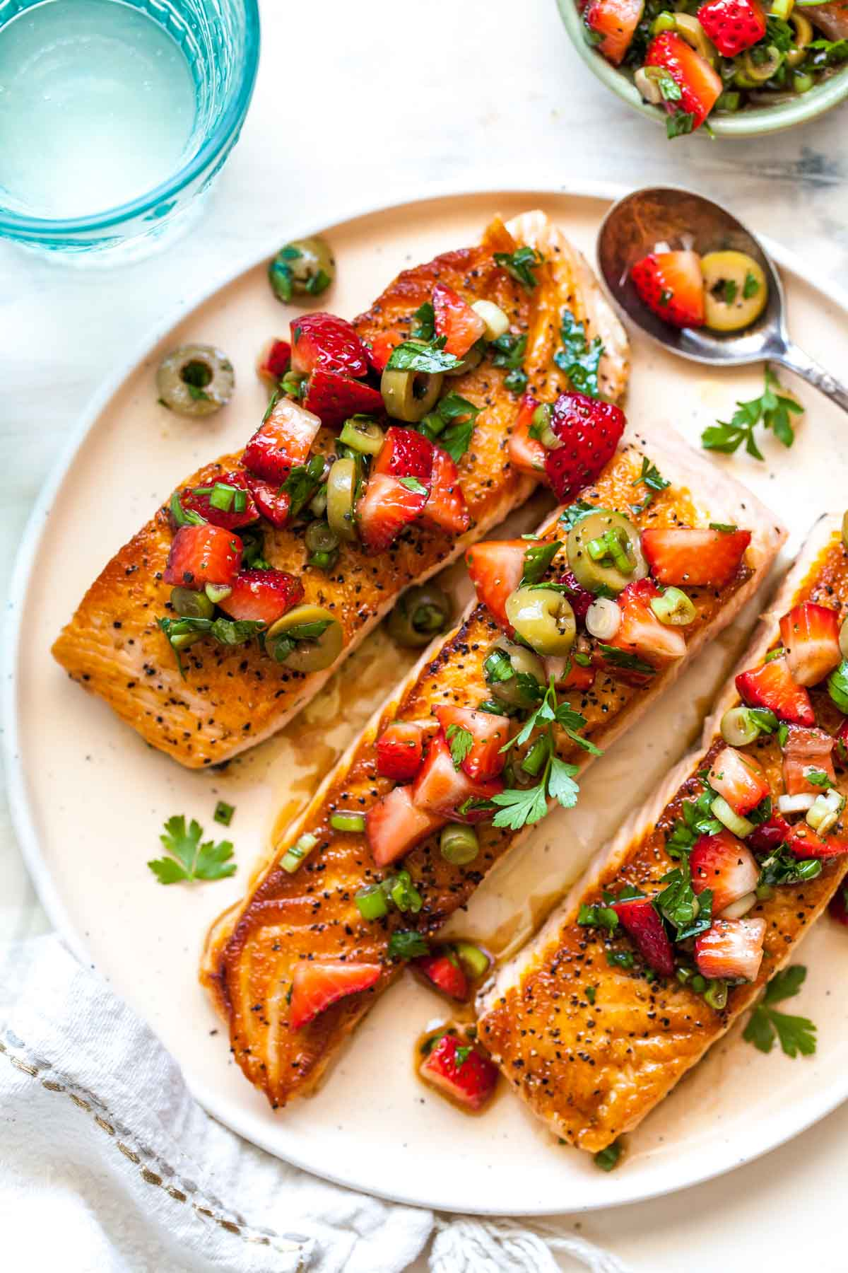Three salmon fillets on a plate topped with strawberry-olive tapenade