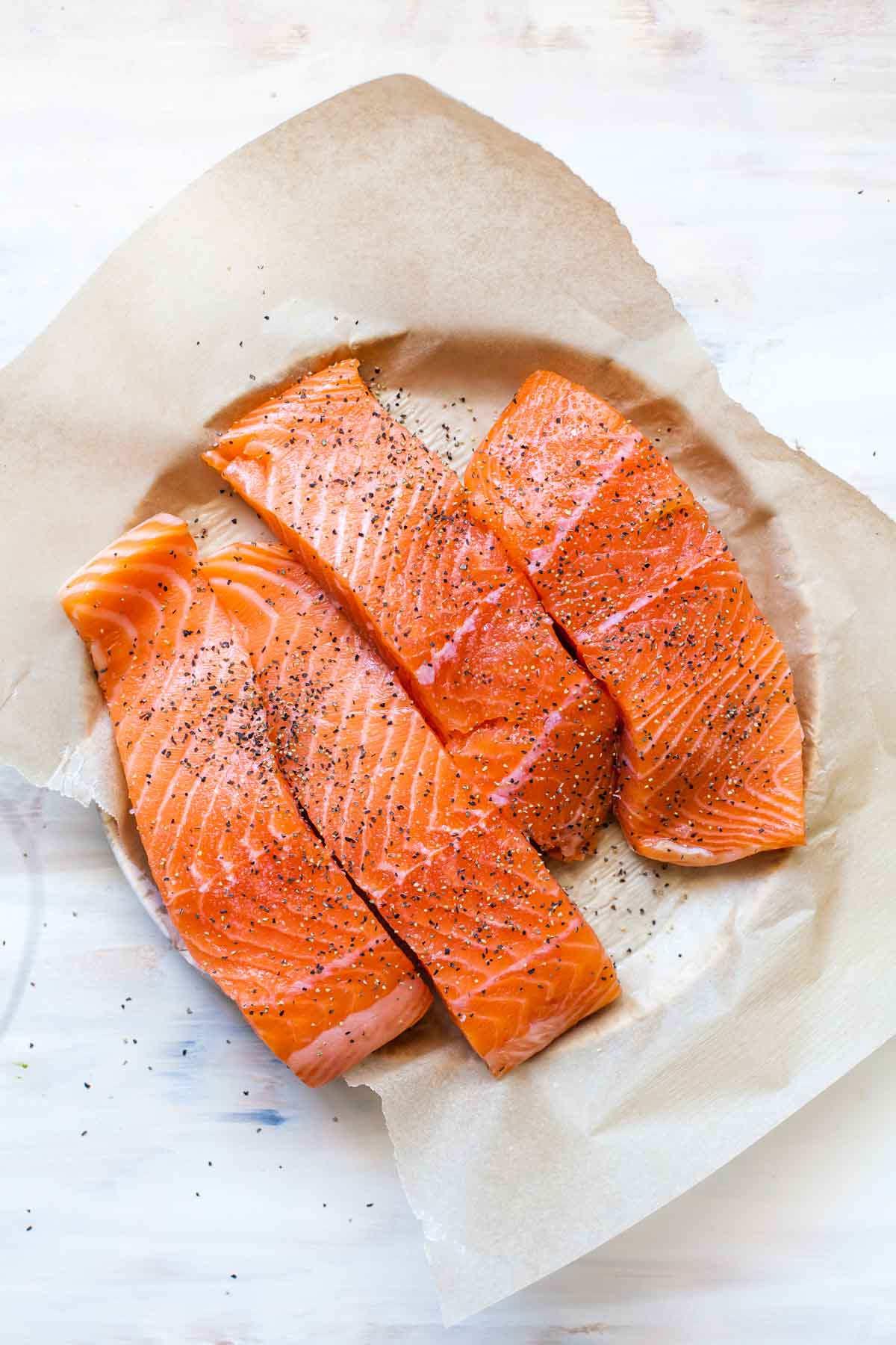 Raw salmon fillets on a plate seasoned with salt and pepper