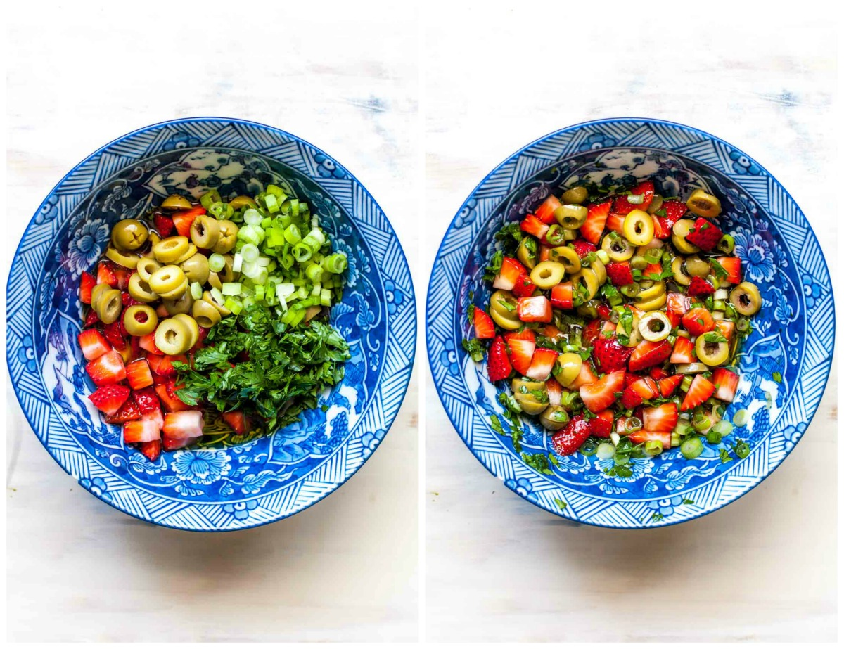 Strawberries, olives, scallions, and herbs in a large blue bowl
