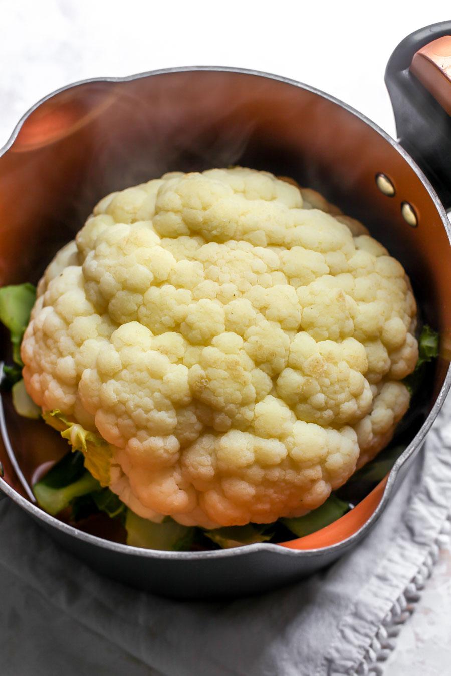 Pesto-Roasted Whole Cauliflower with Creamy Garlic Sauce
