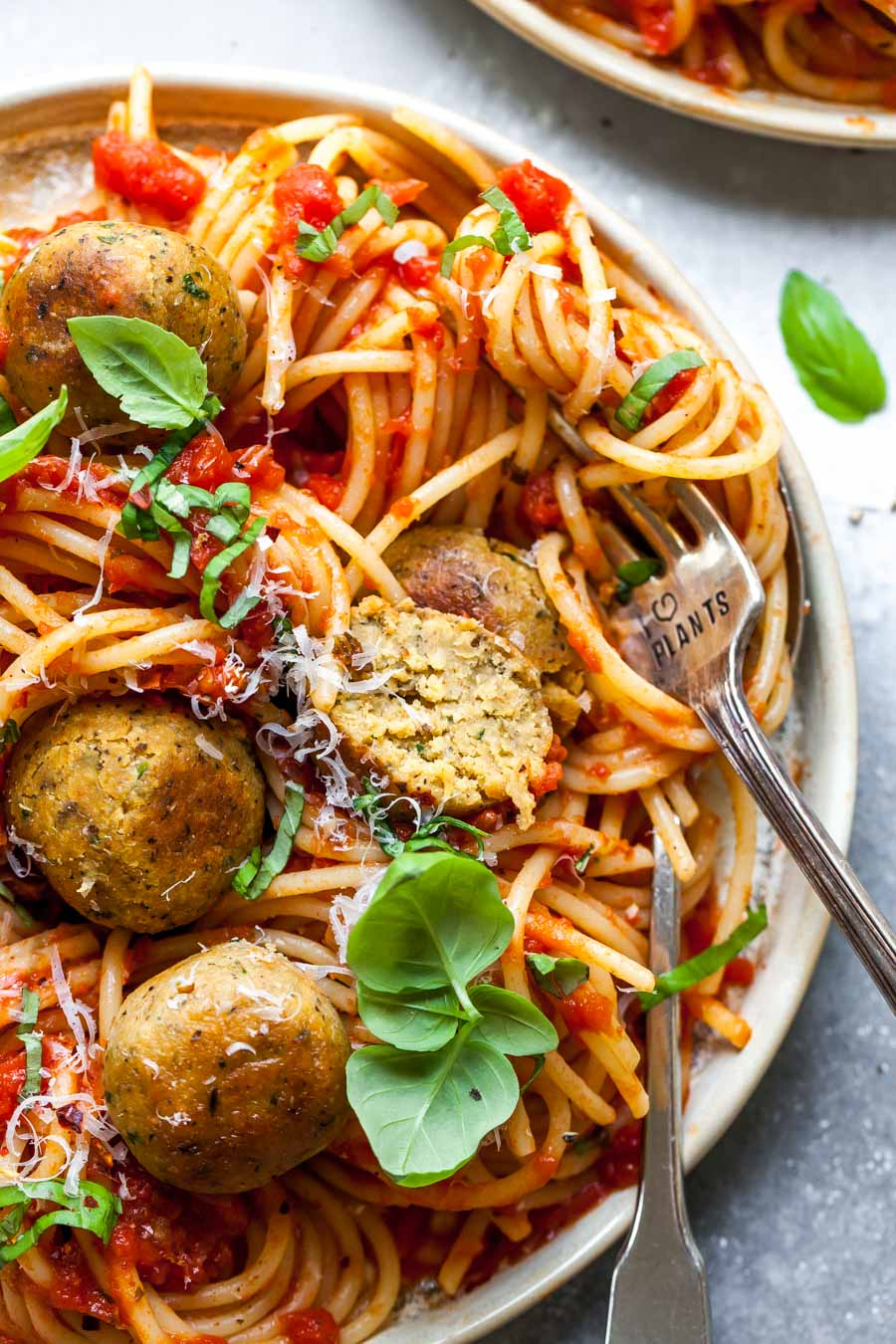Chickpea meatballs on a plate of spaghetti with a fork