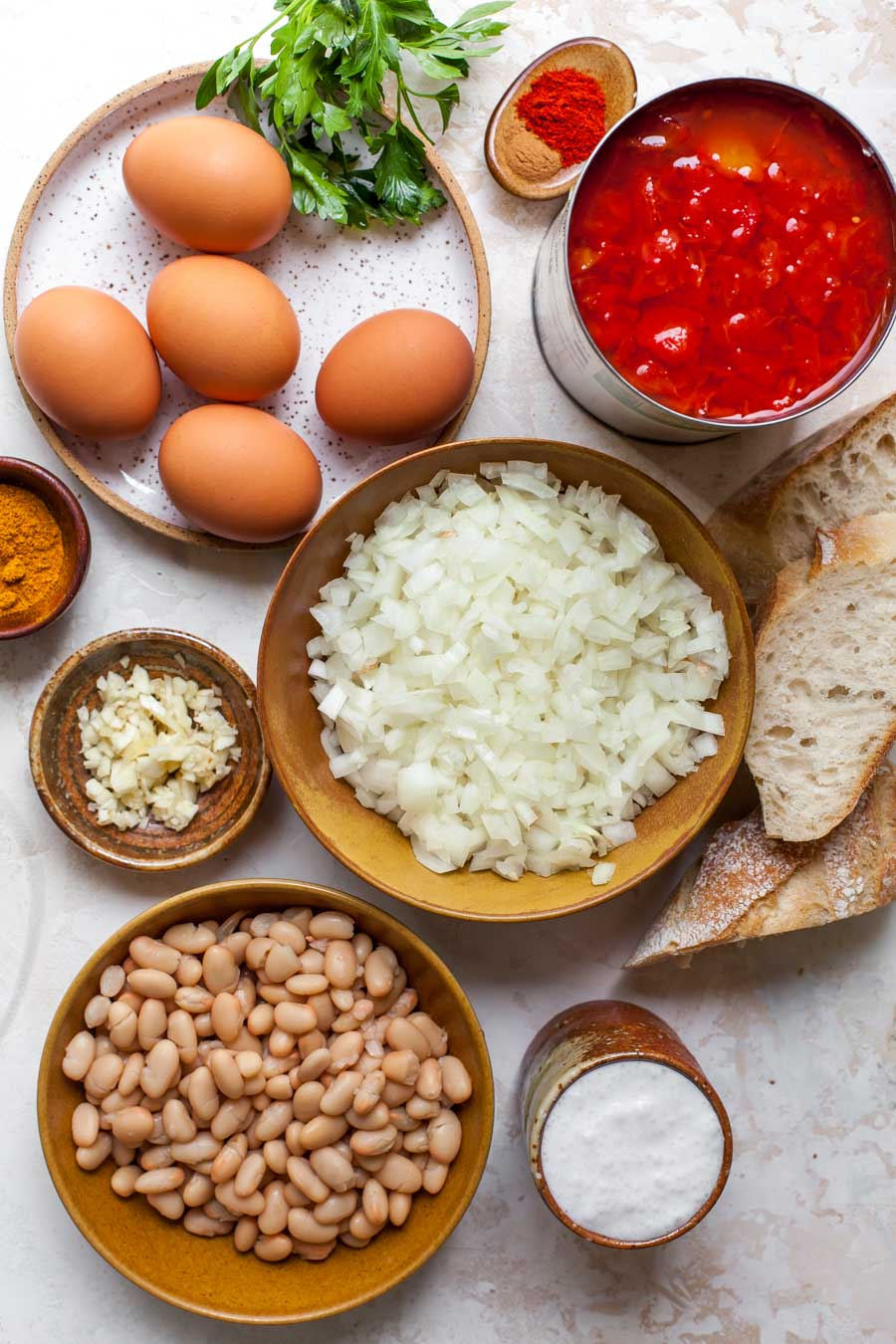 Ingredient overhead shot featuring eggs, spices, onions, tomatoes, and bread