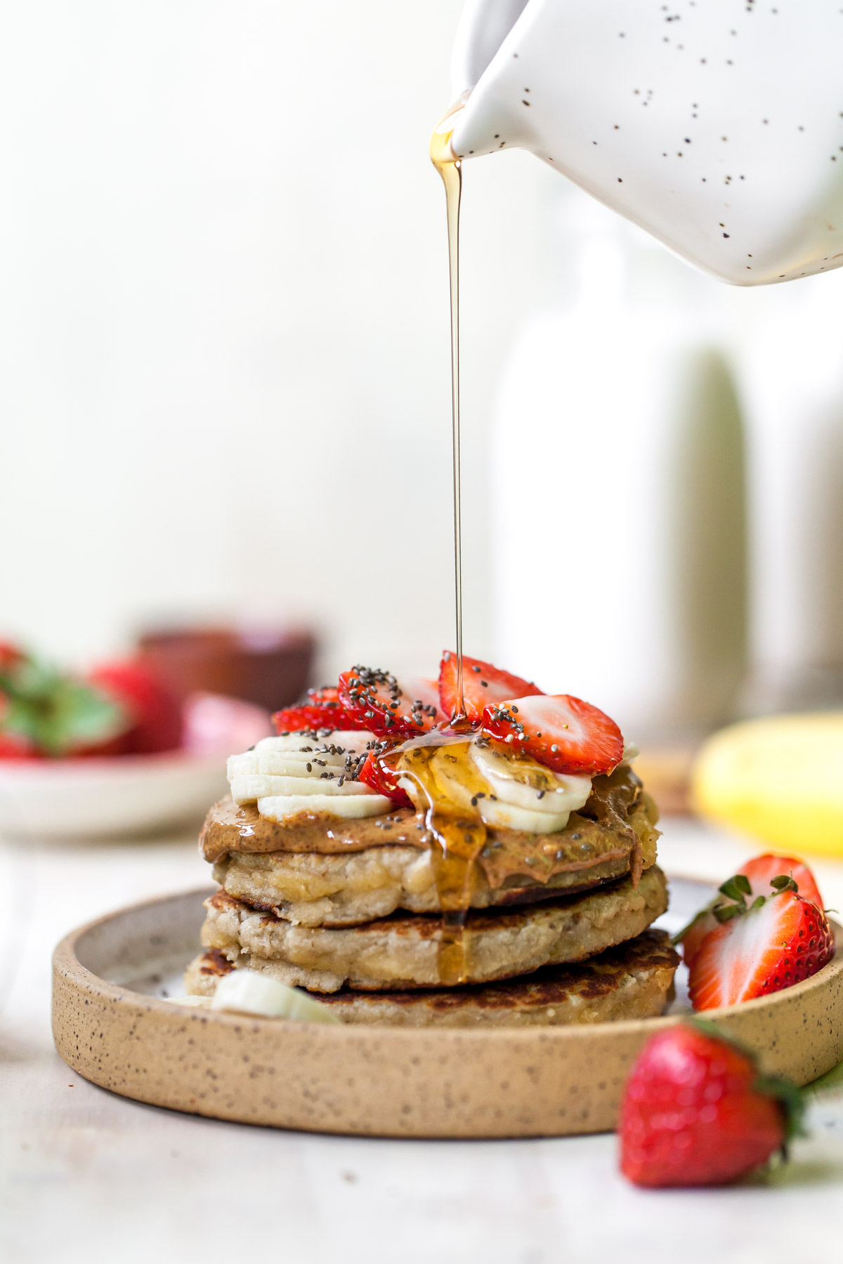 Syrup actively pouring over a stack of three pancakes on a plate