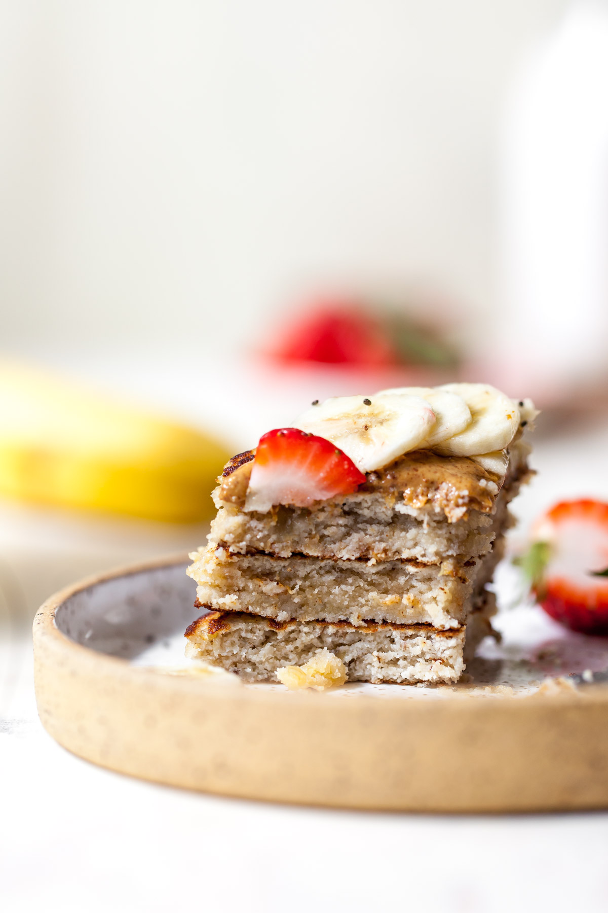 One bite of coconut flour pancakes on a plate topping with banana and strawberry slices