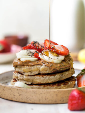 Stack of three coconut flour pancakes on a plate with syrup drizzle overtop