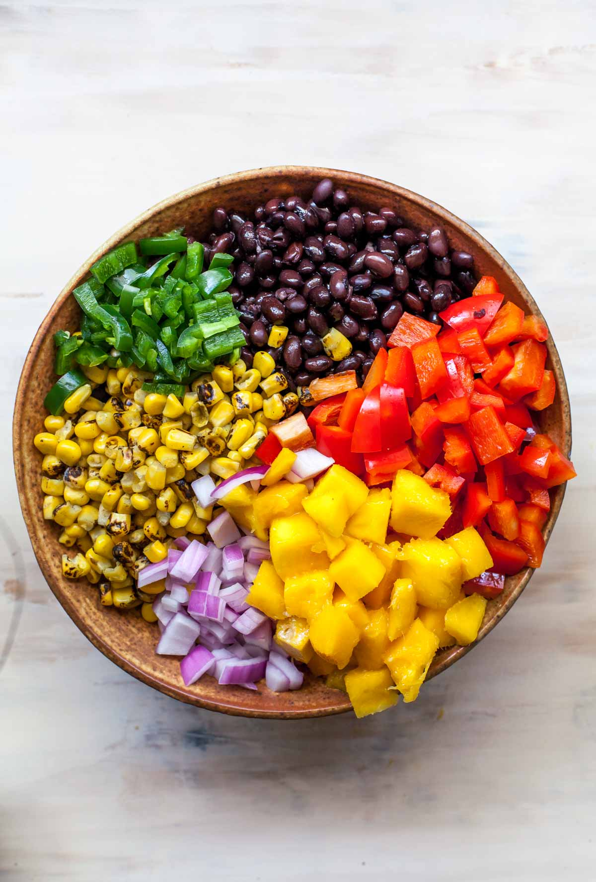 Quinoa, mango, black beans, corn, and bell peppers in a large brown bowl