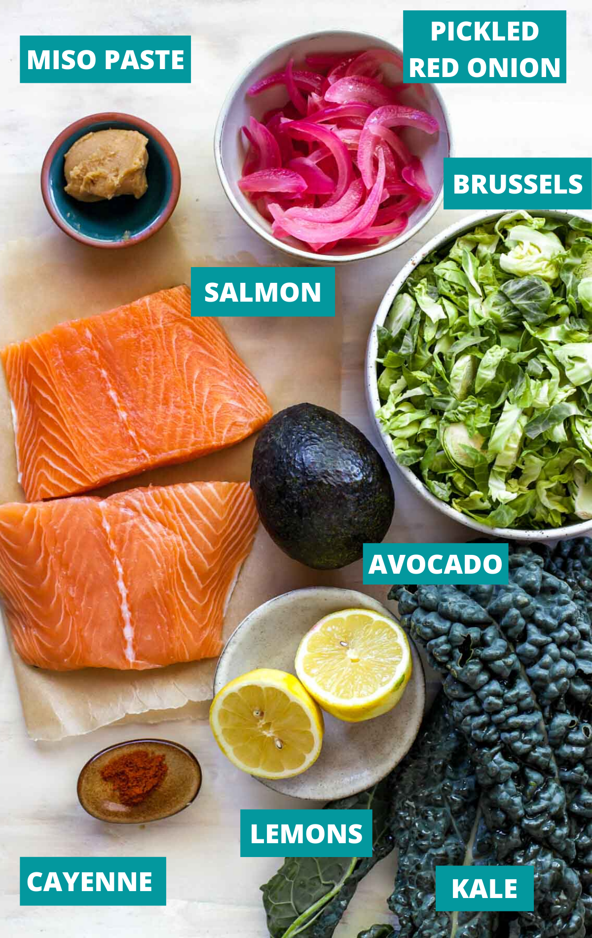 Salmon fillets, kale, brussels, and salad dressing ingredients in separate bowls with ingredient labels