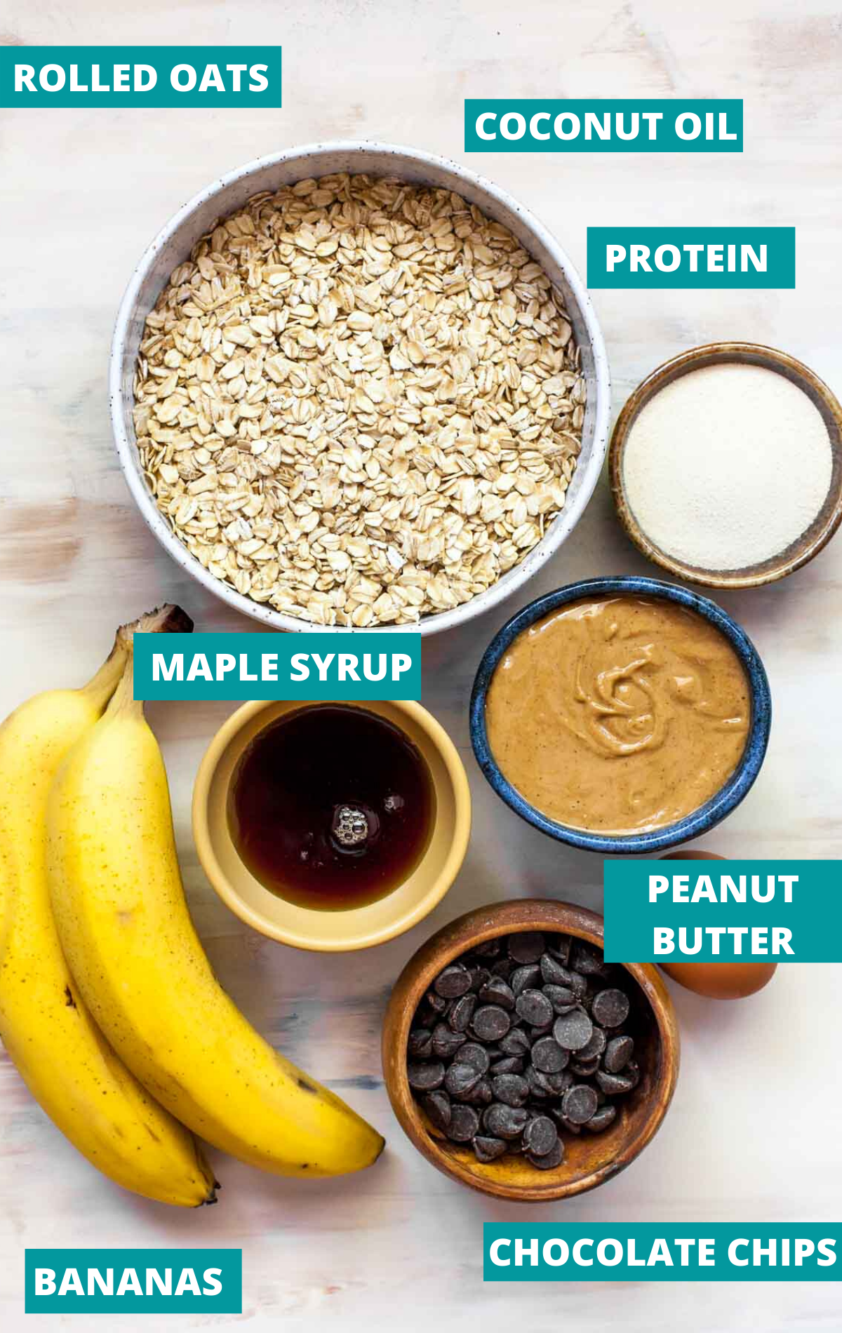 Bananas, oats, peanut butter, maple syrup, and chocolate chips in small bowls on a white surface
