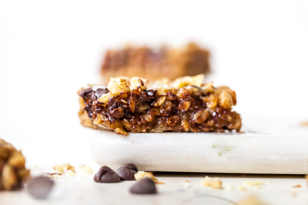 Side view of peanut butter banana oat bars on a white cutting board