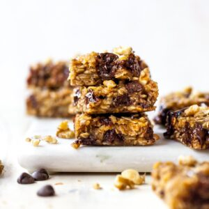 Three peanut butter oat bars stacked on top of one another on a white cutting board