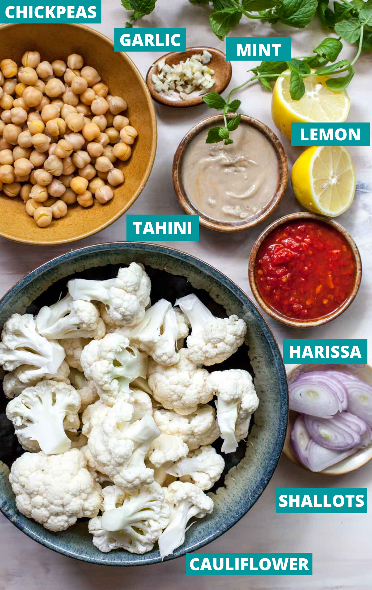 Cauliflower florets, chickpeas, tahini, harissa, and tahini in separate bowls with ingredient label tags