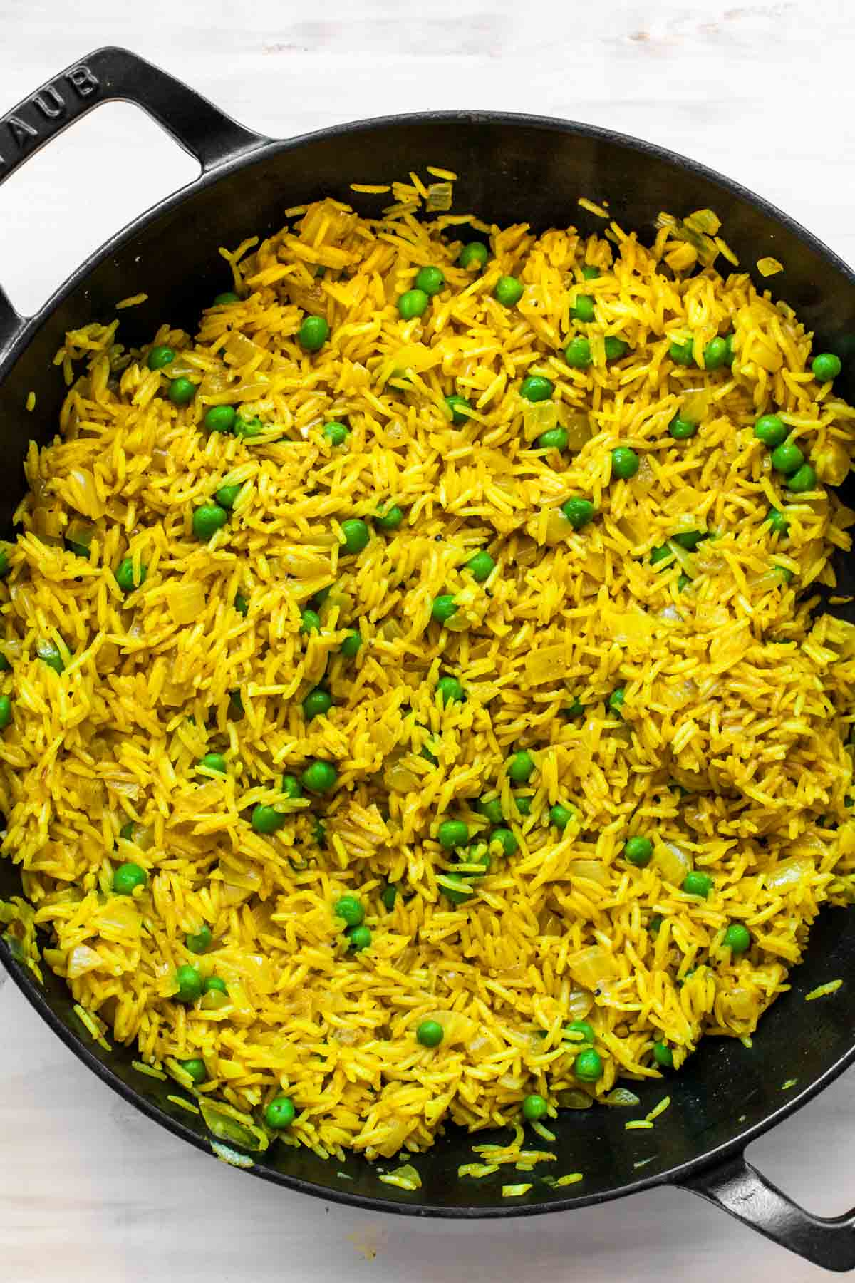 Curried white rice and peas in a large black skillet