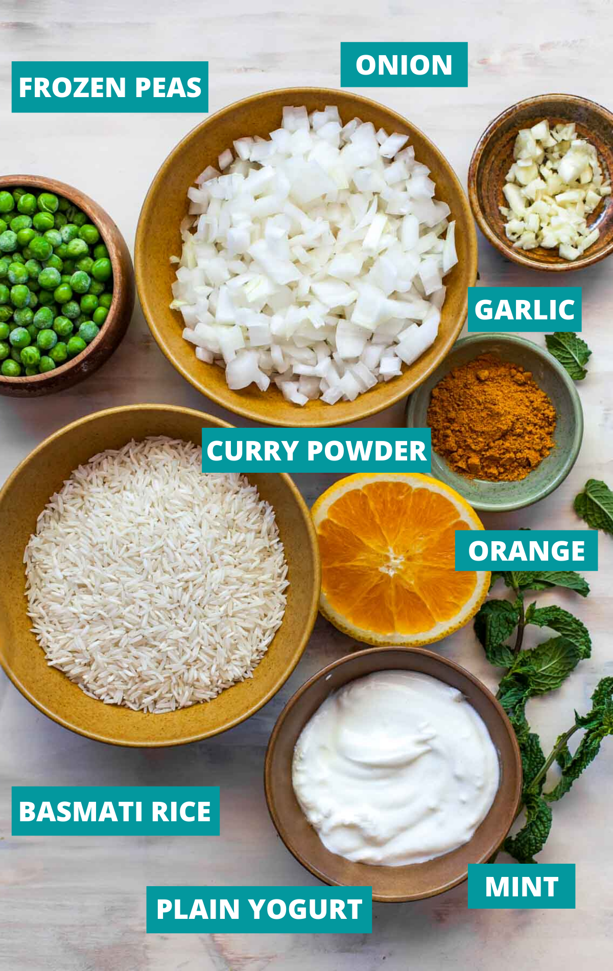 Rice, onion, yogurt, peas, and garlic in separate bowls on a tan board with ingredient labels