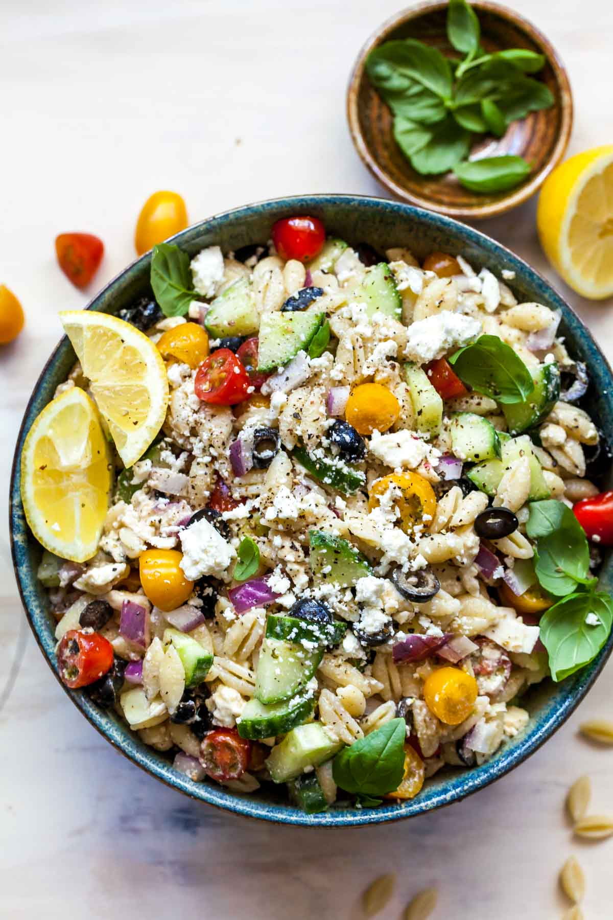 Pasta salad with tomatoes, feta, cucumber and basil garnish in a black bowl