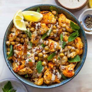 Roasted cauliflower, chickpeas, lemon wedges, and mint with tahini dressing in a black bowl
