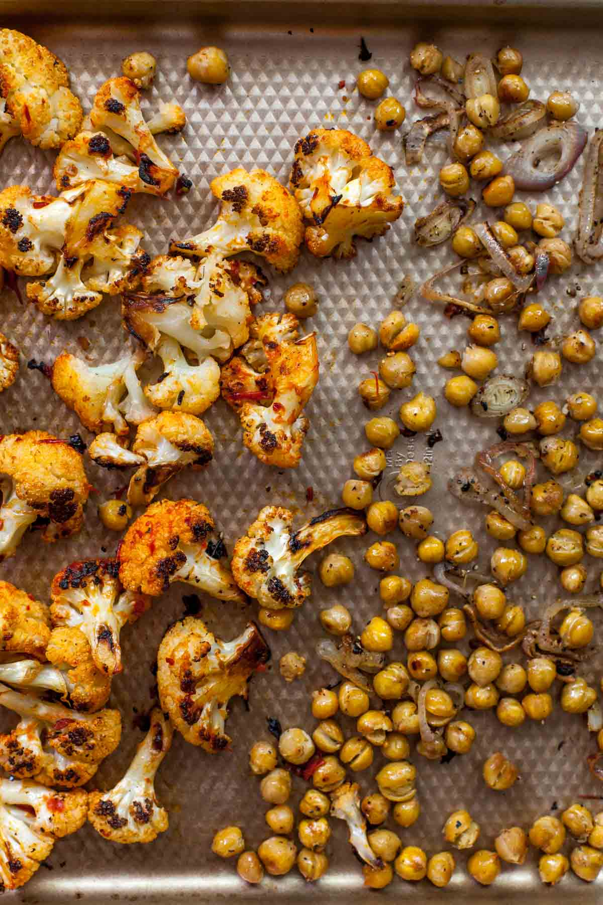 Roasted cauliflower and chickpeas on a baking sheet