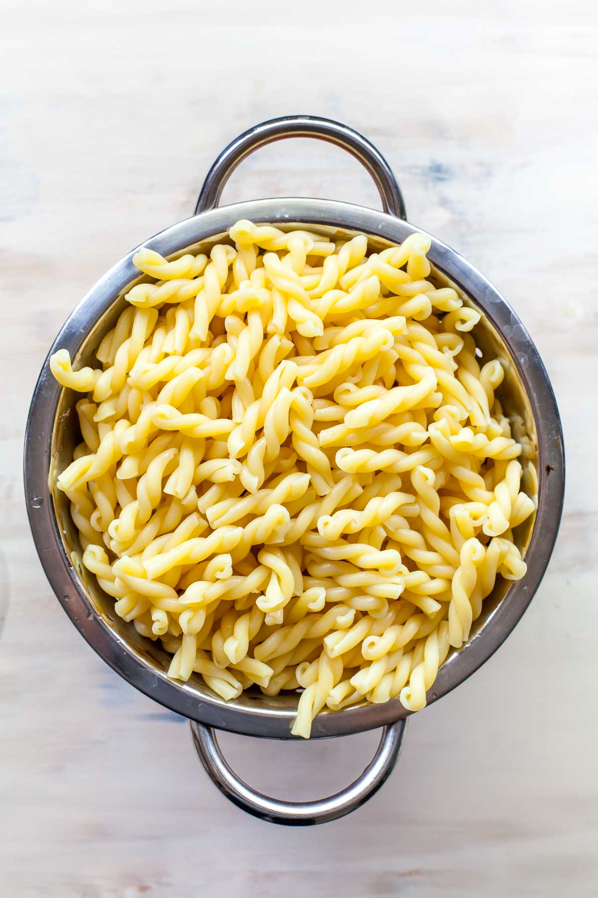 Cooked gemelli pasta in a colander on a tan surface