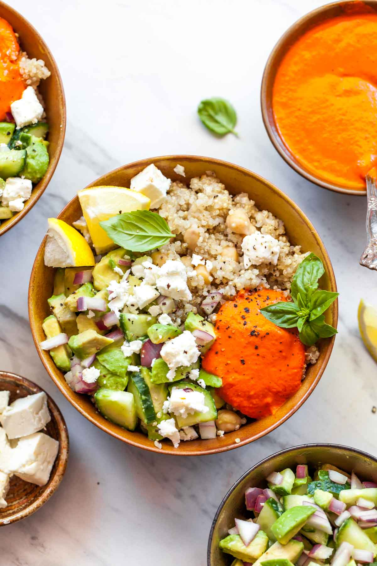 Quinoa, chickpeas, and avocado salad in a gold bowl topped with orange red pepper sauce and basil