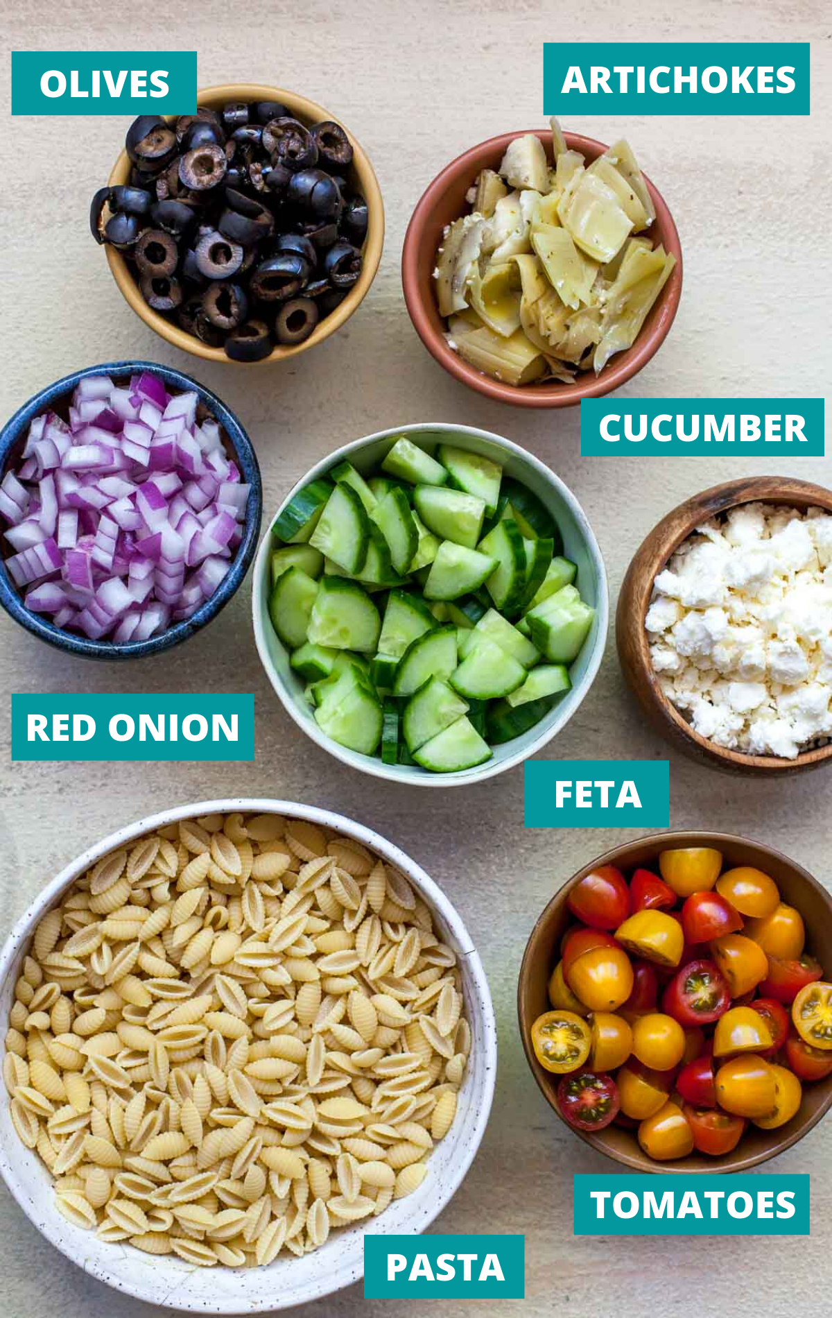 Pasta and veggies in separate small bowls on a tan board with ingredient tags