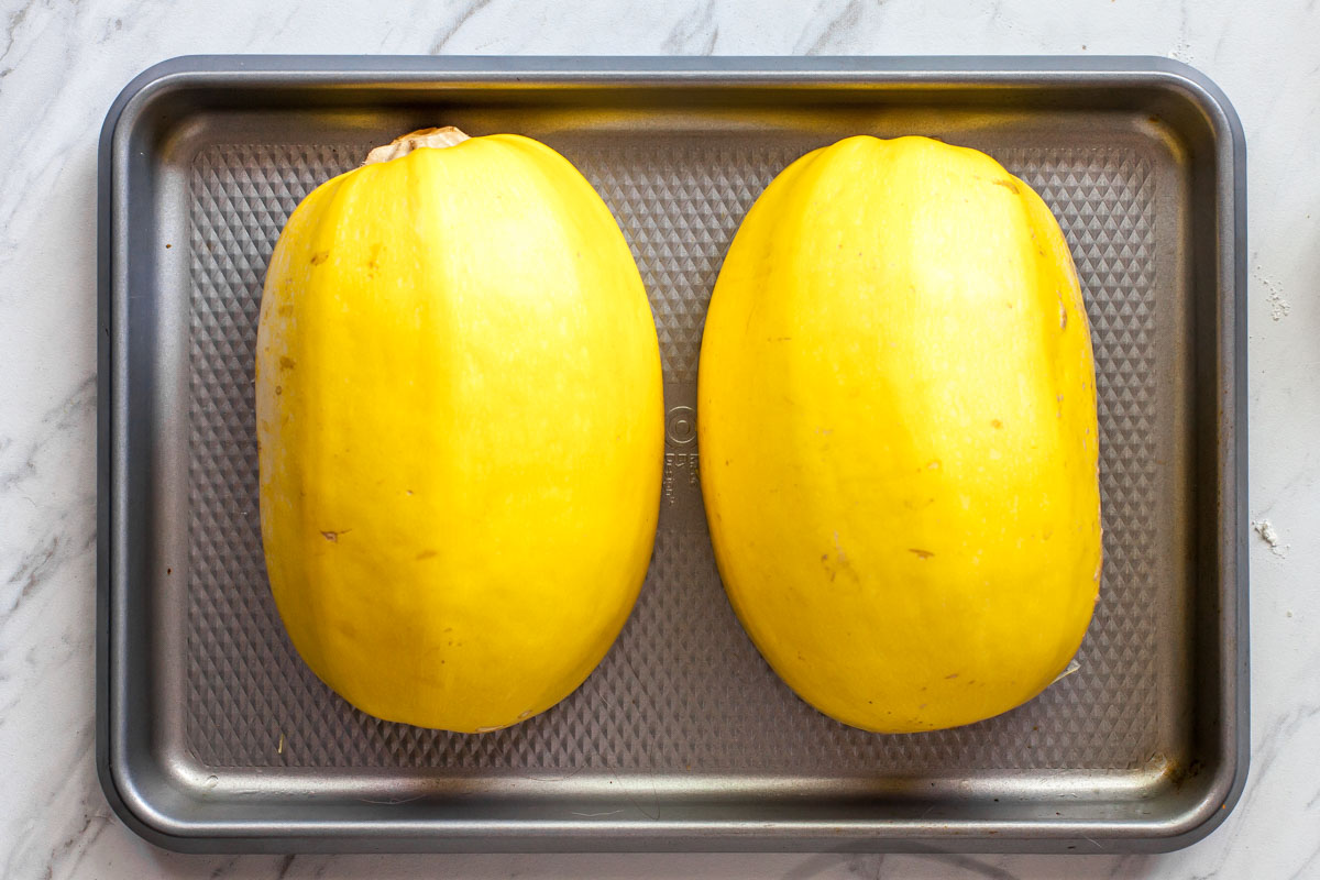Two spaghetti squash halves flesh side-down on a silver baking sheet