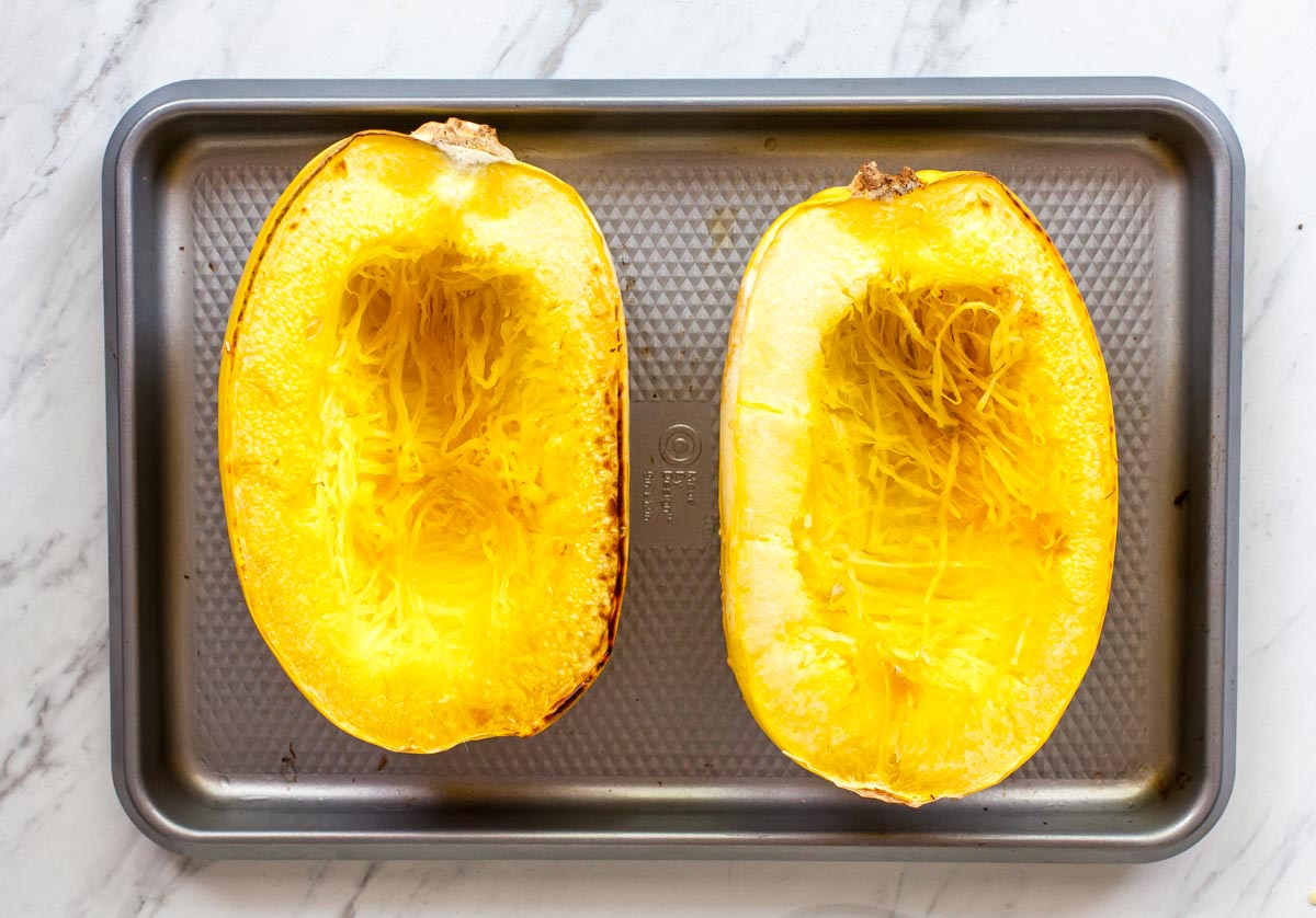 Two spaghetti squash halves facing up on a silver baking sheet