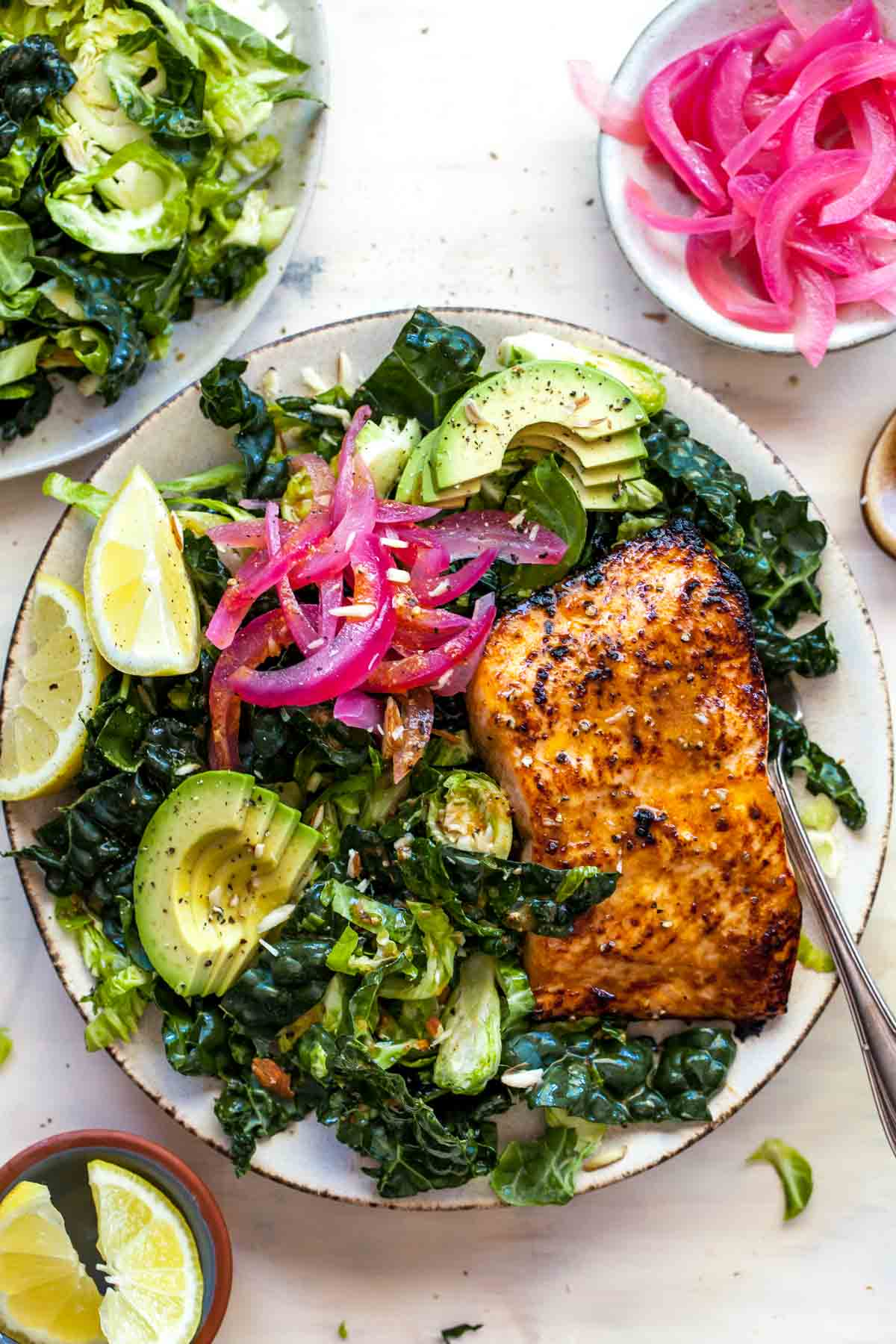 miso-glazed salmon fillet over kale and shredded brussels sprouts on a tan plate