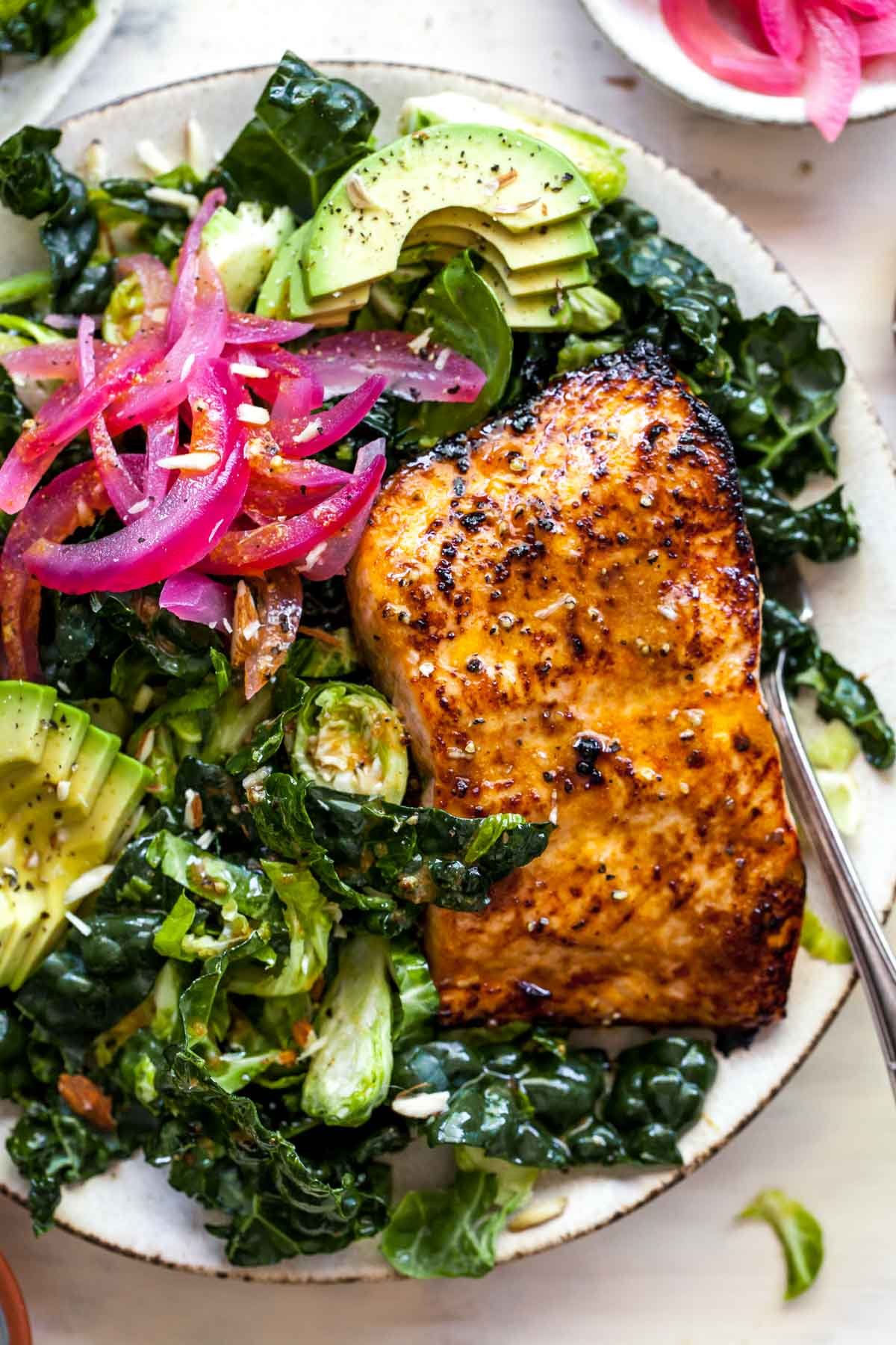 Close up view of cooked salmon fillet over kale salad with pickled red onion on top