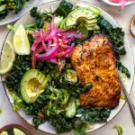A plate of greens topped with sliced avocado, pickled red onion, and salmon fillet.