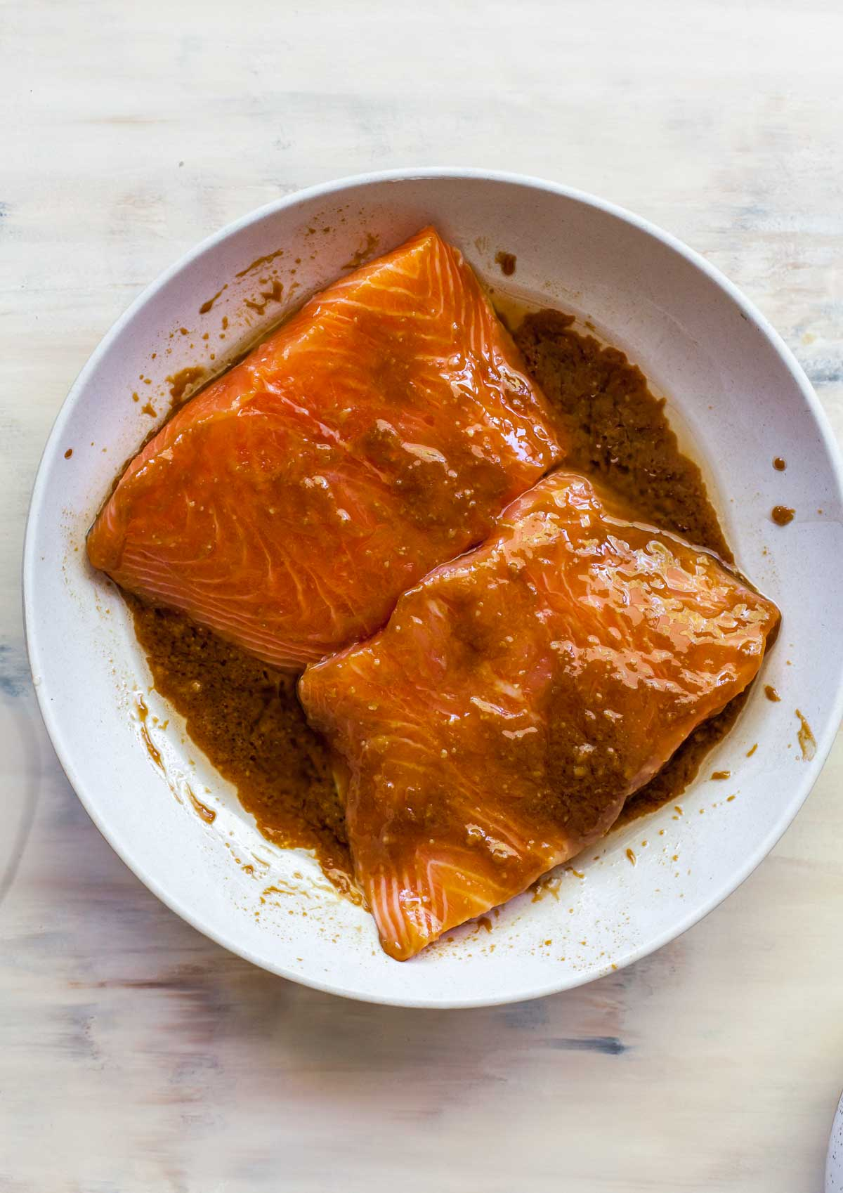 Raw salmon fillets in a bowl covered in miso marinade