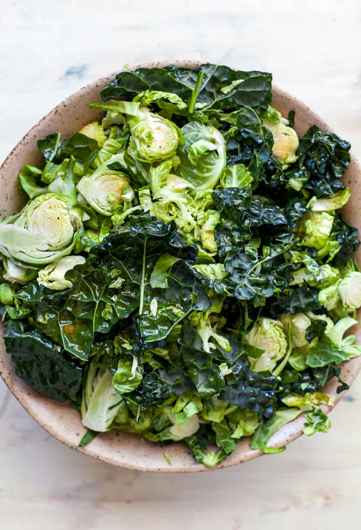 Shredded Brussels sprouts and chopped kale in a large tan bowl