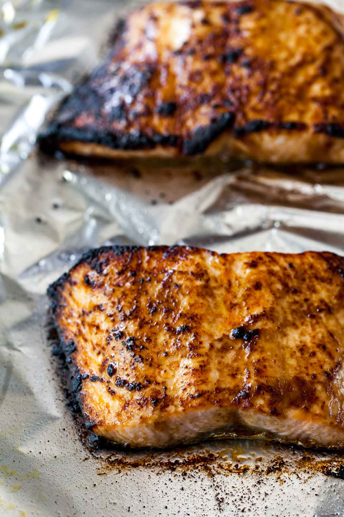 Broiled salmon fillets on a baking pan covered in foil