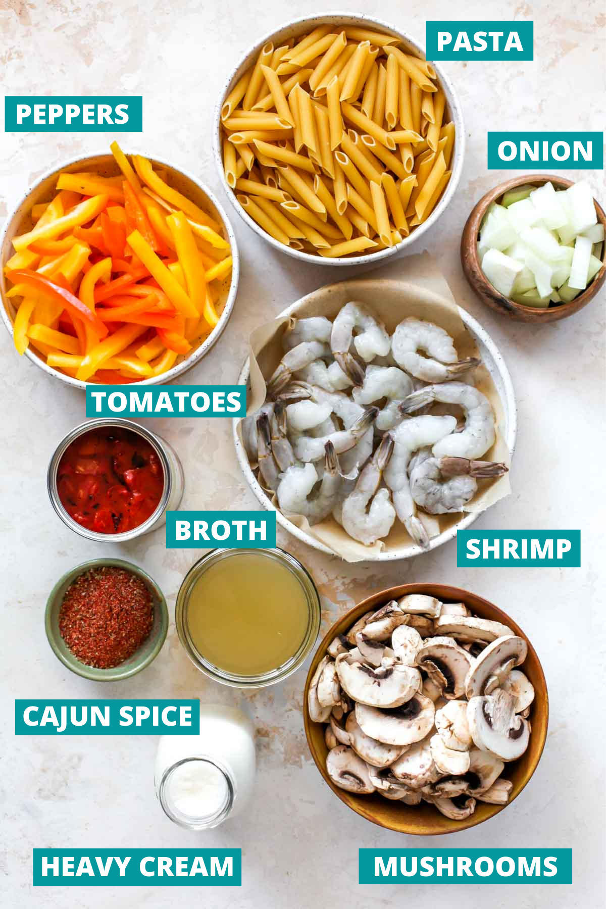 Shrimp, pasta, vegetables, and cajun spice in separate bowls with ingredient labels