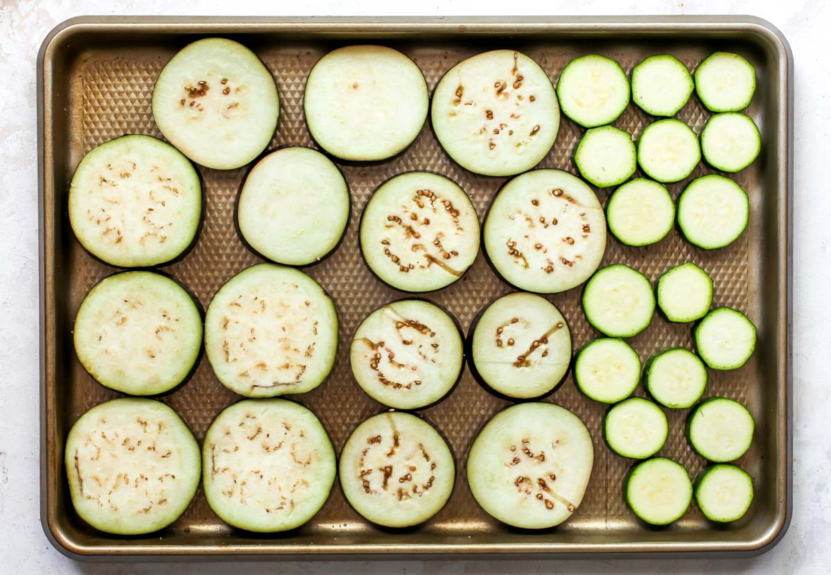 Sliced eggplant and zucchini on a large baking sheet