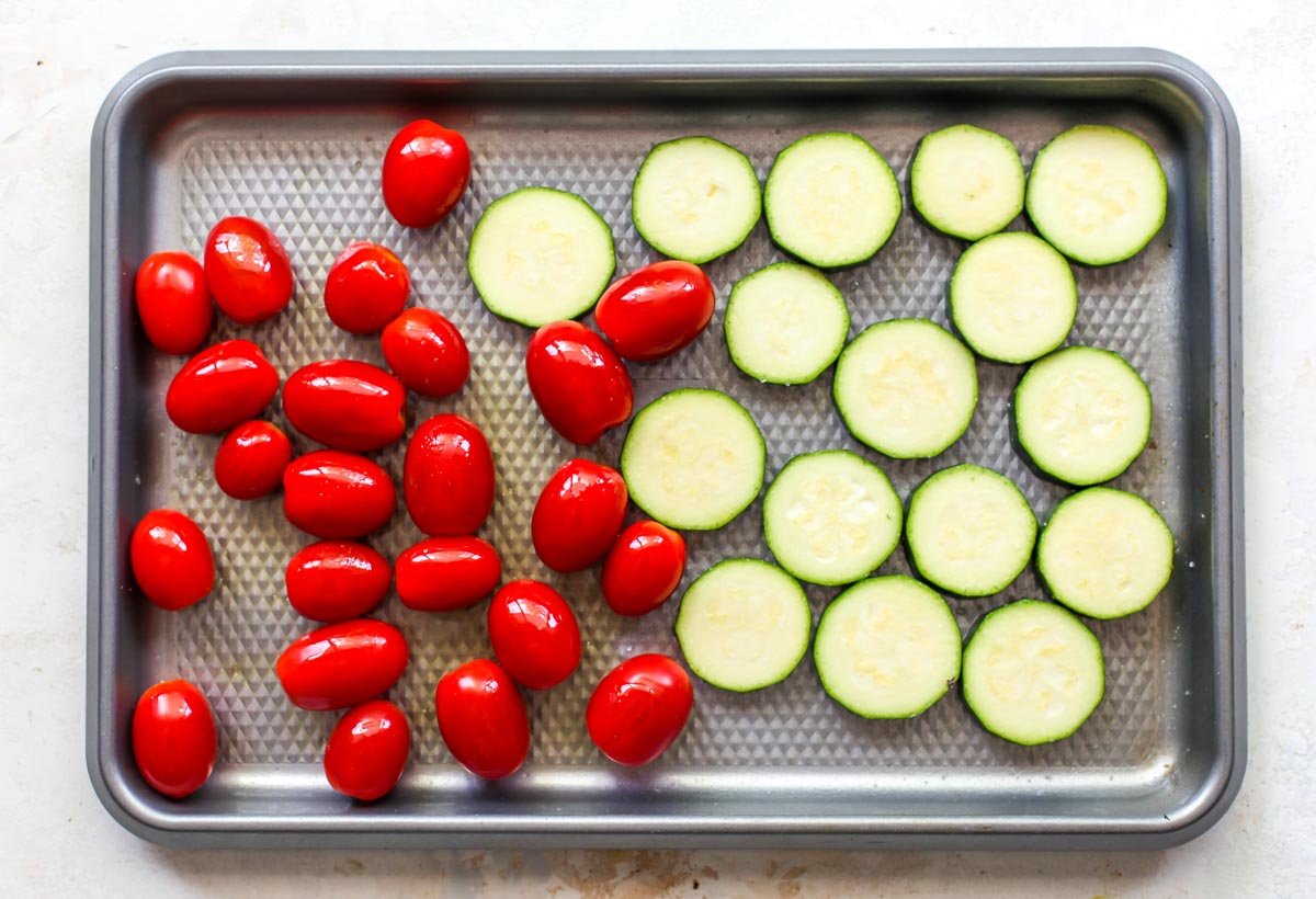 Sliced zucchini and tomatoes on a large baking sheet