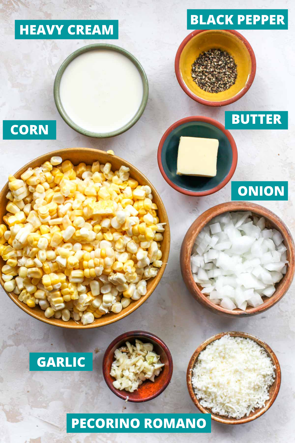 Corn, cheese, butter, and black pepper in separate bowls with blue ingredient label tags