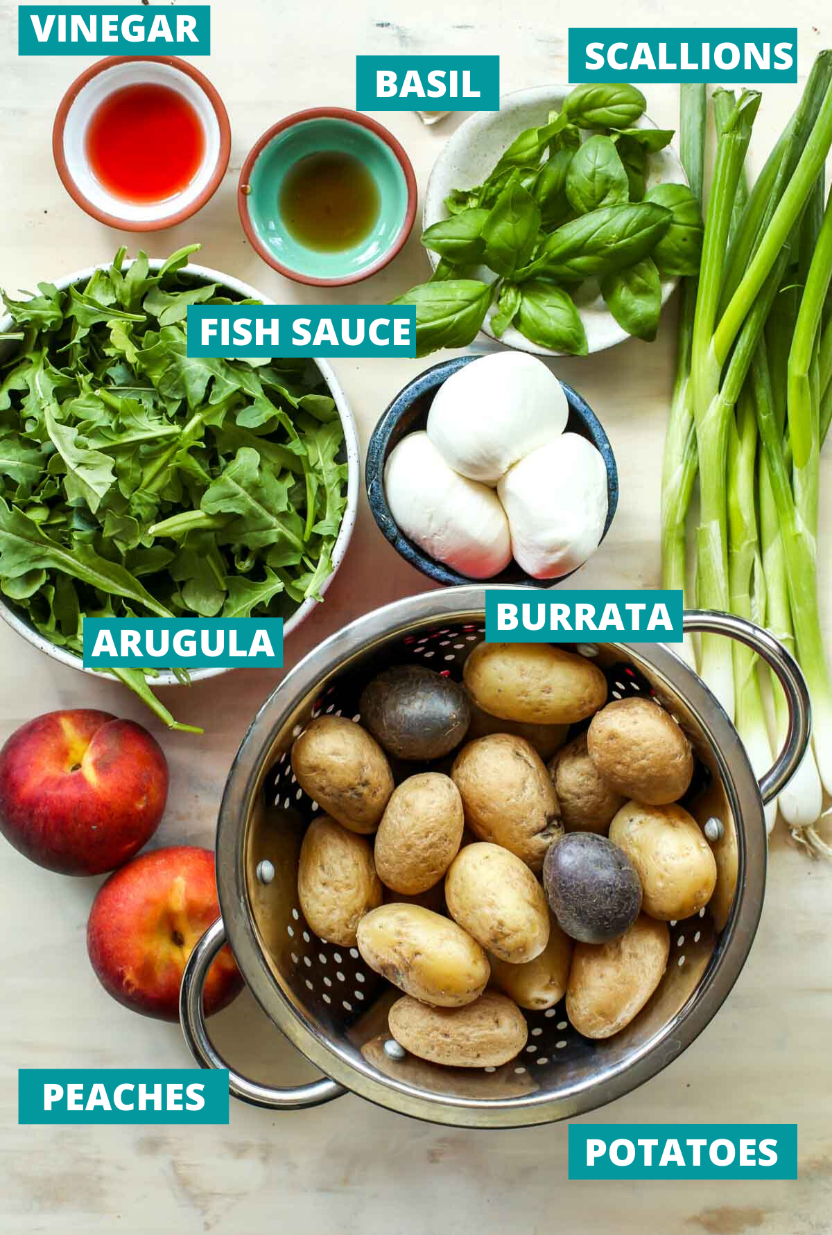 Baby potatoes, arugula, peaches, and burrata in separate bowls with ingredient tags