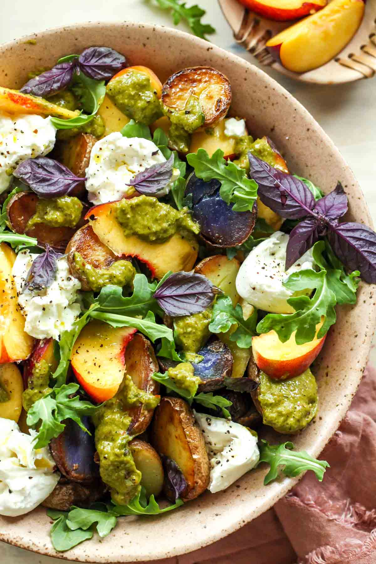 Potato and peach salad topped with scallion dressing in a peach bowl