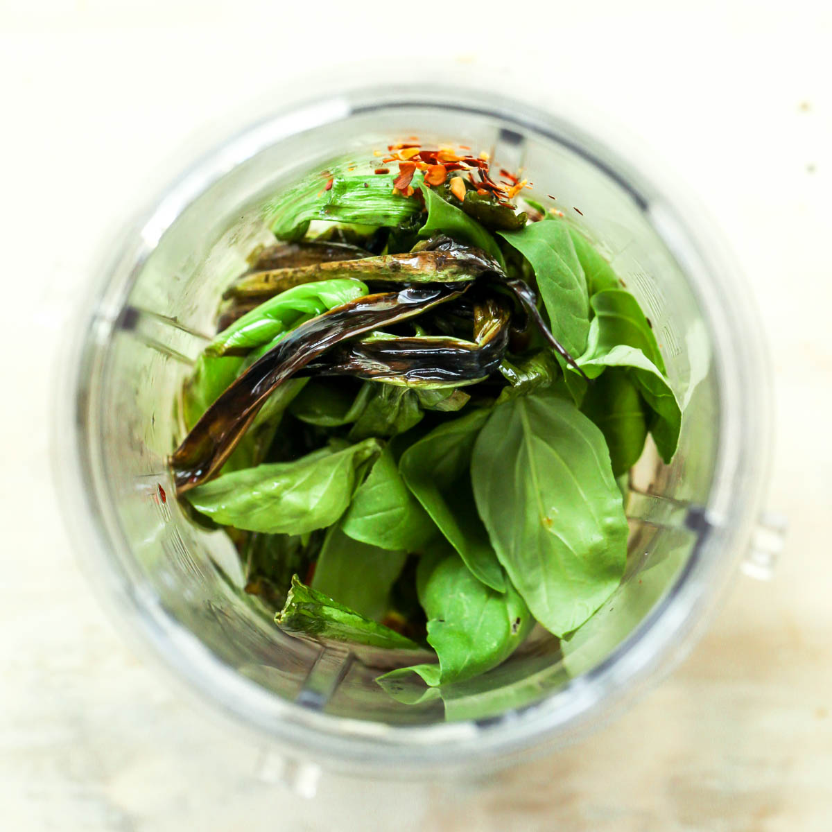 Basil, scallions, red pepper flakes, and olive oil in a mini blender