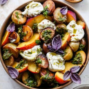 Potato, peaches, and burrata in a bowl topped with scallion dressing and basil