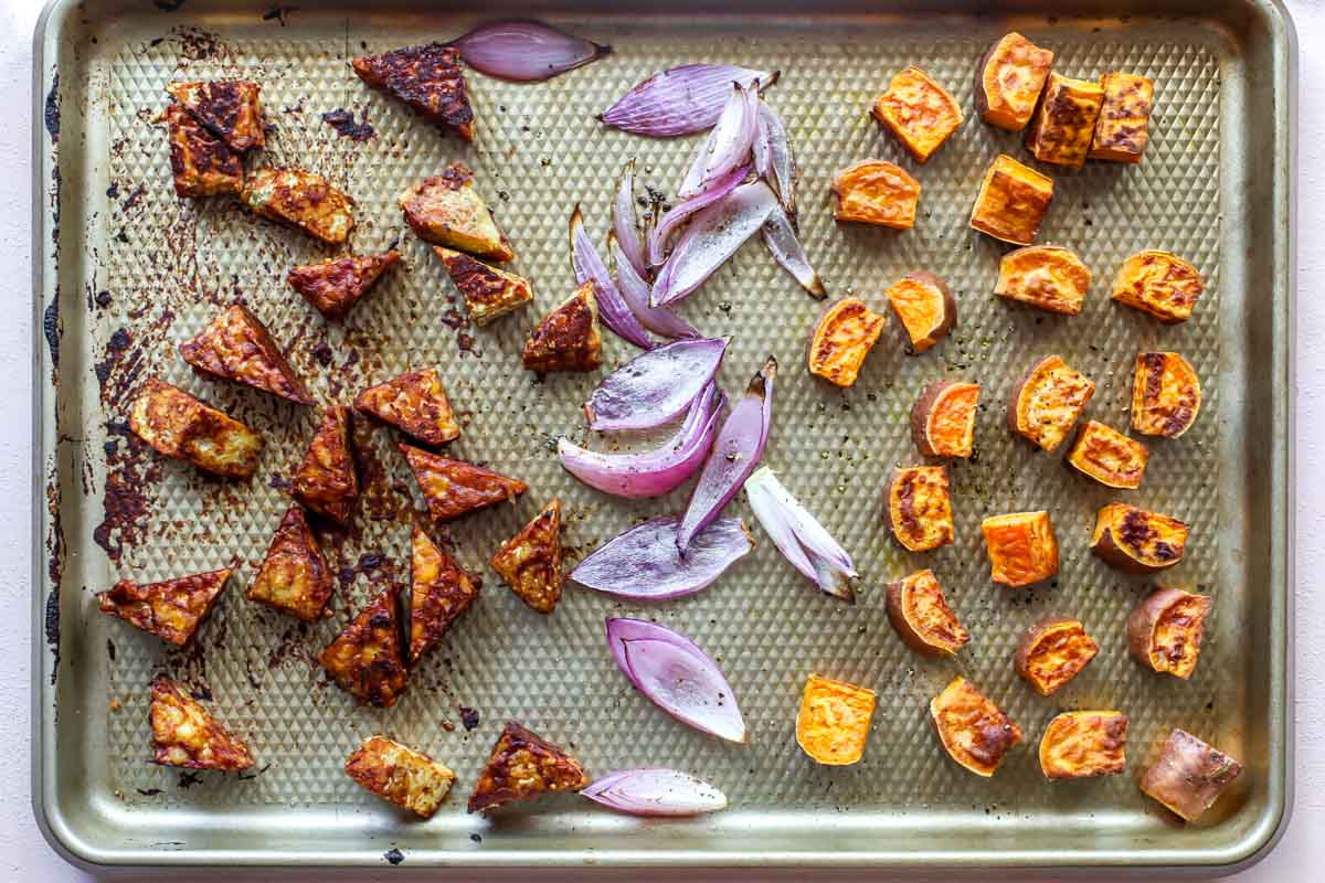 Tempeh, red onion, and cubed sweet potato separated on a baking sheet