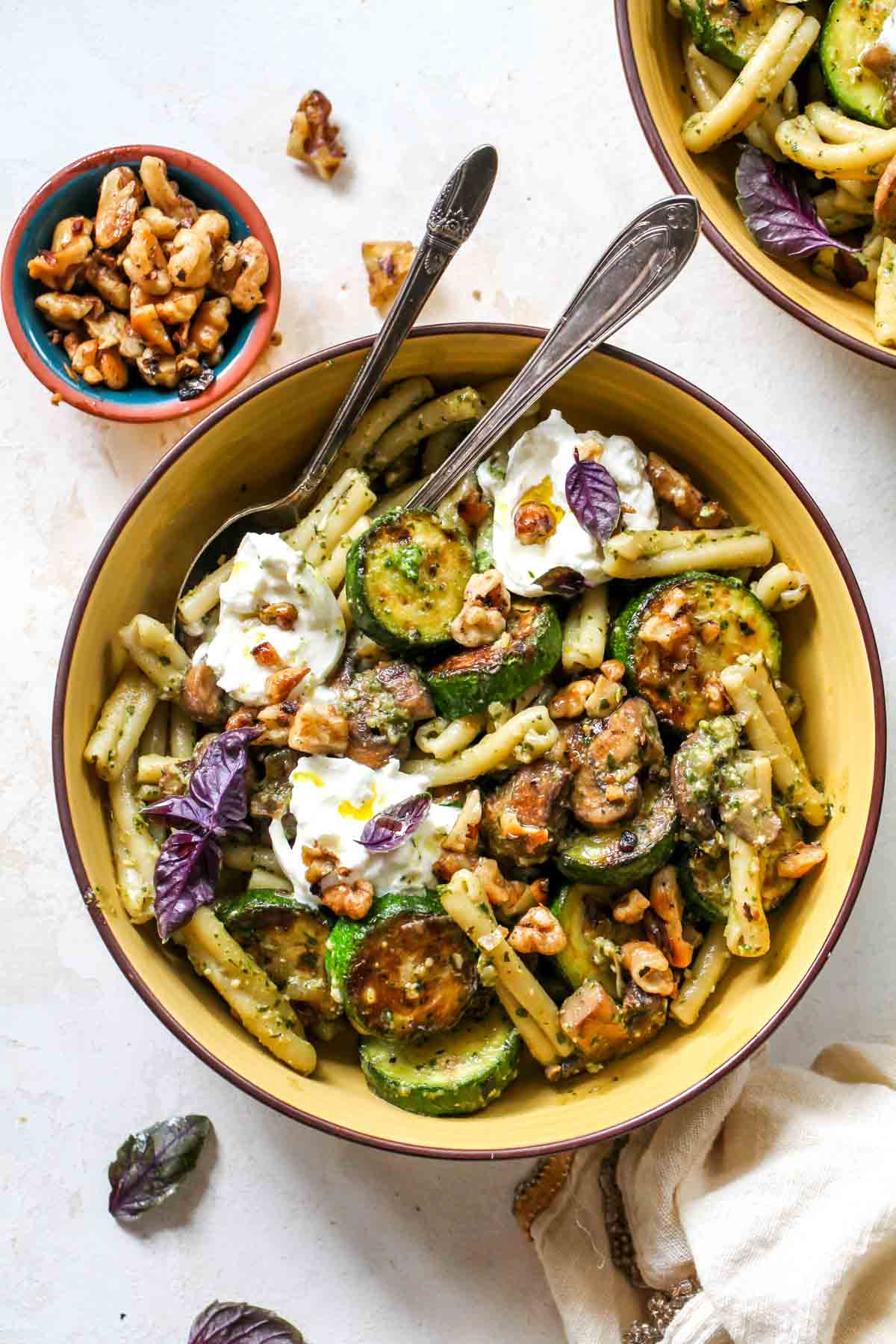 Pesto pasta in a yellow bowl with zucchini and mushrooms