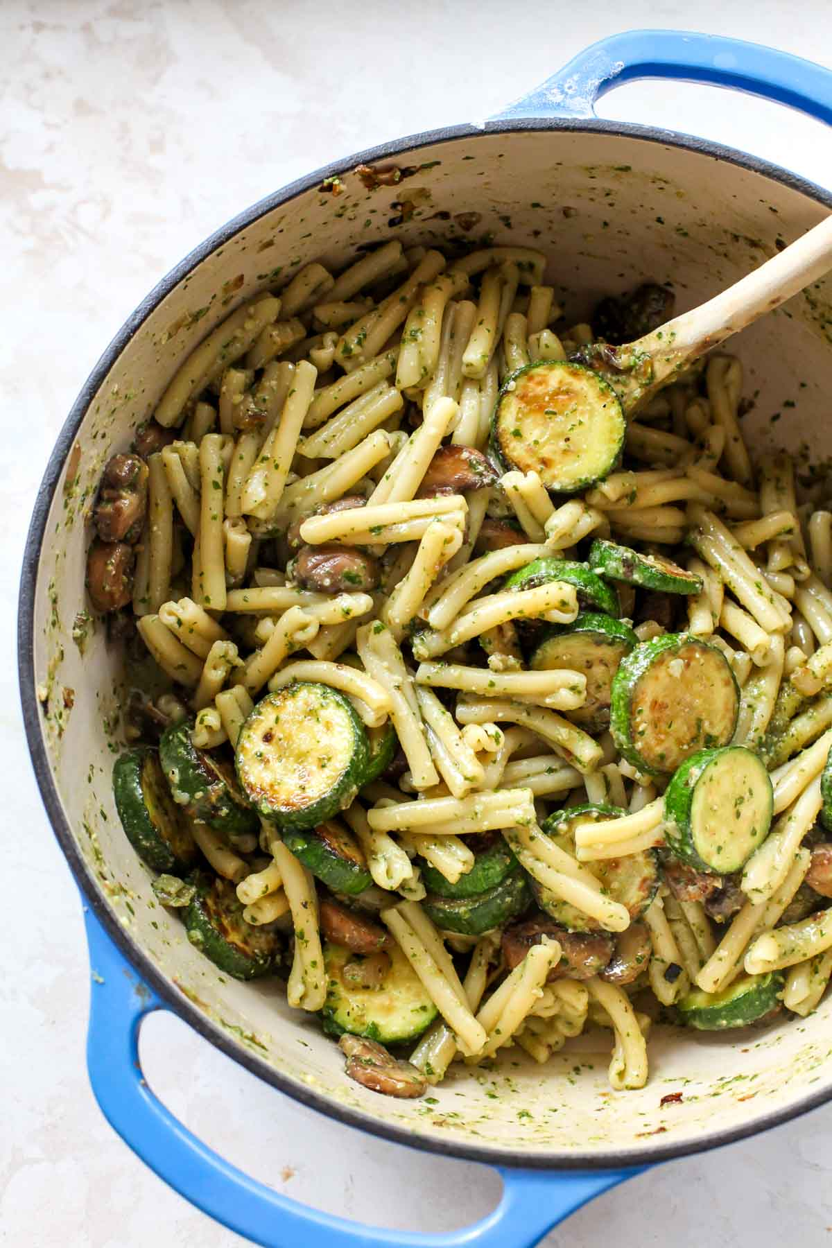 Pasta mixed with pesto and zucchini in a large blue pot with a wooden spoon