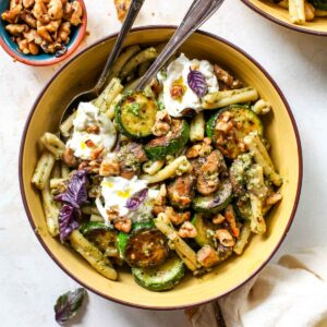 Pesto pasta with zucchini and mushrooms in a yellow bowl