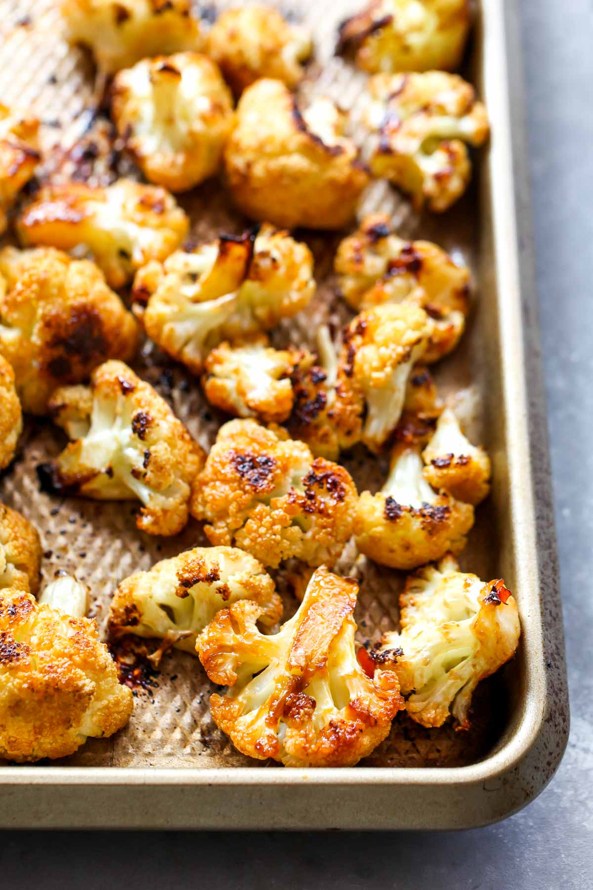 Roasted cauliflower florets on a gold baking sheet